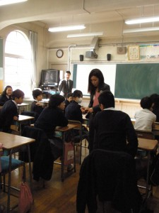 弁護士バッヂを持ち教室内を移動する白井弁護士。学生たちも思わず覗きこみます